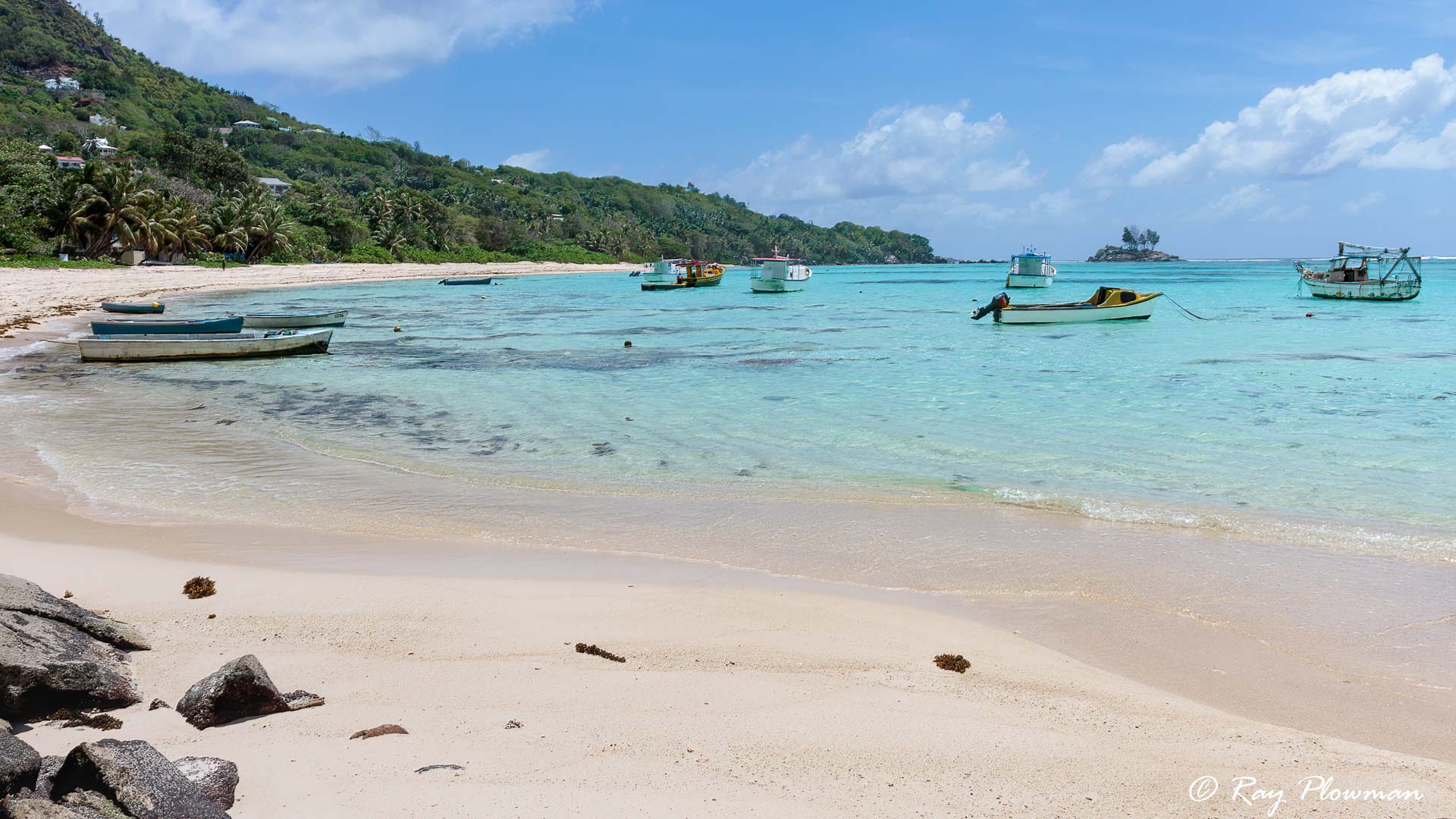 Fishing boats and Ile Souris at Anse Royale on Mahé island in Seychelles